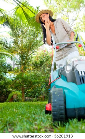 Home garden grass cutting woman mowing with lawn mower in tropical green - stock photo