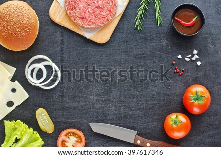Home handmade hamburger. Raw minced beef (patty), sesame bun, slice of cheese, tomato, onion rings, pickle, lettuce, herbs and BBQ sauce. Black board background. Space for text. - stock photo