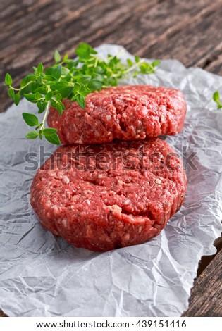 Home HandMade Raw Minced Beef steak burgers on scrumbled paper - stock photo