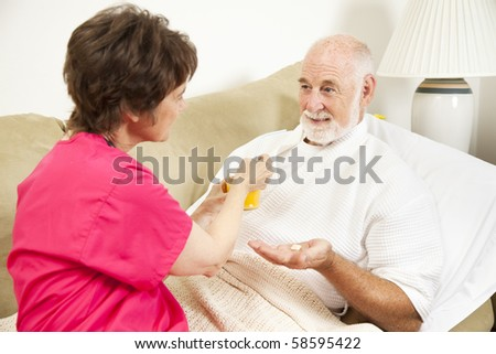 Home health nurse giving an elderly patient juice to make his medicine go down. - stock photo