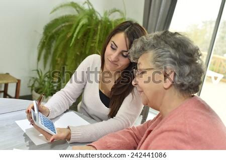 Home helper taking care of elderly woman's paperwork - stock photo