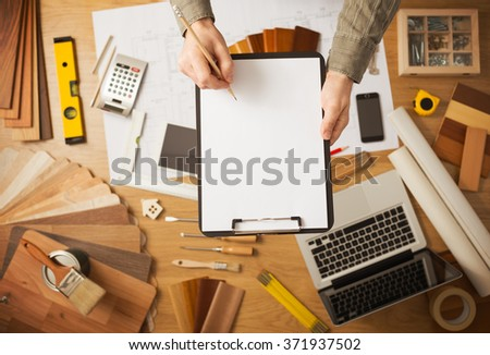 Home improvement and renovation concept with hands holding a blank clipboard and work desktop on background, top view - stock photo