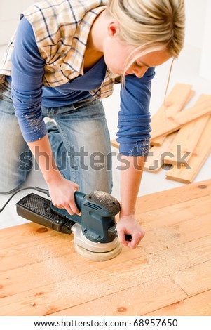 Home improvement - handywoman sanding wooden floor in workshop