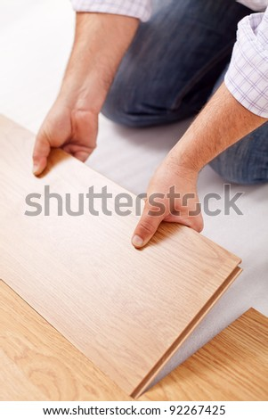 Home improvement - installing laminate flooring, fitting a plank - stock photo