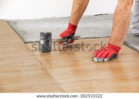Home improvement, renovation - construction worker tiler is tiling, ceramic tile floor adhesive, trowel with mortar - stock photo