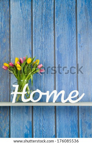 Home in white letters with colorful bouquet tulips in pink and yellow isolated on background - stock photo