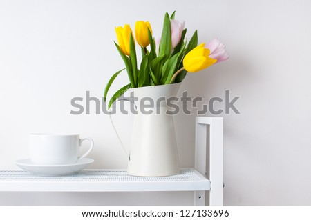 home interior decoration: a bouquet of tulips in a jug and a cup and saucer on white shelves - stock photo
