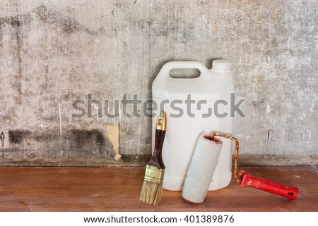 Home interior room repair concept - old gray concrete wall and dirty brown floor in repairing room with white plastic can, paint roller and brush near the wall close-up view  - stock photo