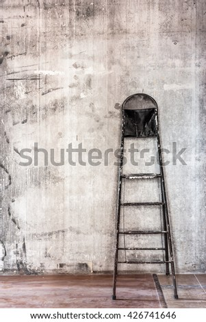 Home interior room repair concept - old gray concrete wall and dirty brown floor in repairing room with old dirty black step ladder near the wall closeup view  - stock photo