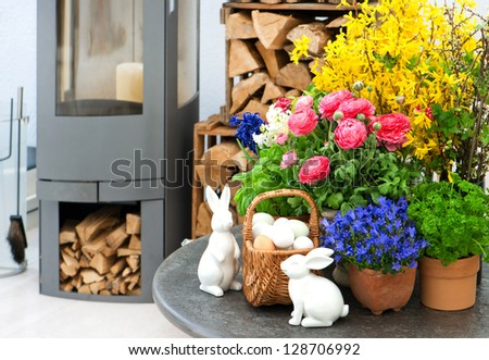home interior with spring flowers and easter decoration. ranunculus, campanula, forsythia - stock photo