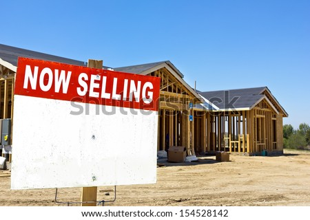 Home is still under construction with a sell sign in the foreground.  - stock photo