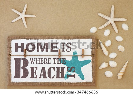 Home is where the beach is distressed wooden sign with starfish and shell selection on sand background. - stock photo