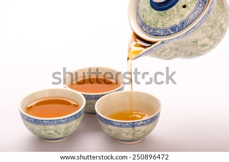 Home is where the tea is. Beautiful composition of Chinese traditional crockery teapot and cups isolated on white background with selective focus - stock photo