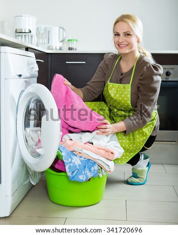 Home laundry. Happy blonde woman loading clothes into a washing machine at the home