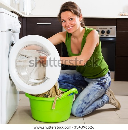 Home laundry. Happy brunette woman loading clothes into washing machine in home - stock photo