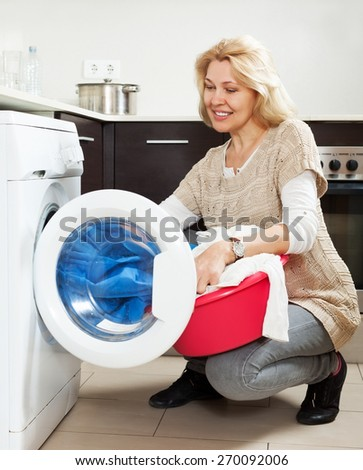 Home laundry. Smiling Housewife using washing machine at home - stock photo