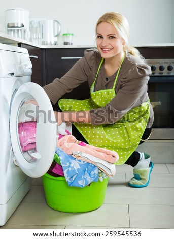 Home laundry. Smiling russian girl using washing machine at home - stock photo
