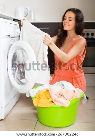 Home laundry. Smiling young housewife using washing machine at home