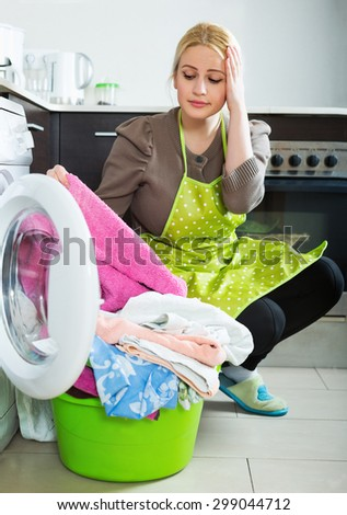 Home laundry. Unhappy blonde woman using washing machine at home - stock photo