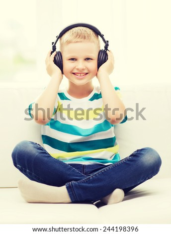 home, leisure, new technology, childhood and music concept - smiling little boy with headphones at home - stock photo