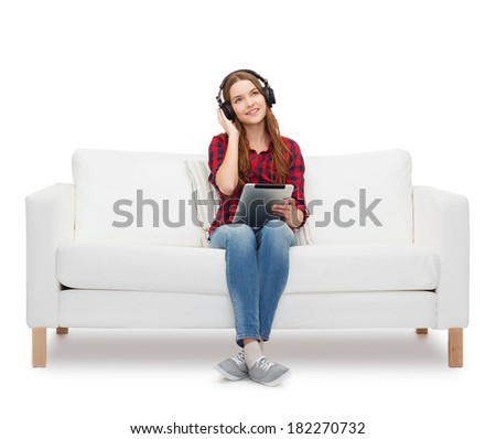 home, leisure, technology and happiness concept - smiling teenage girl sitting on sofa with headphones and tablet pc computer - stock photo