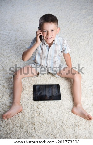 home, leisure, technology and internet concept -Smiling boy indoor. Sitting on the floor with digital tablet and talking on the phone - stock photo