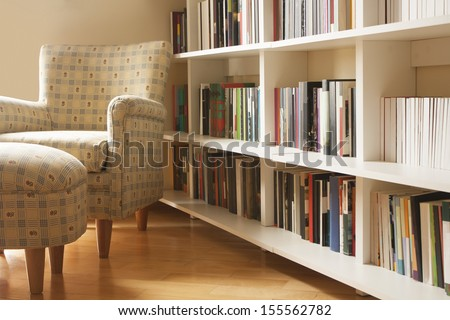 Home library with arm chair. Clean and modern decoration. - stock photo