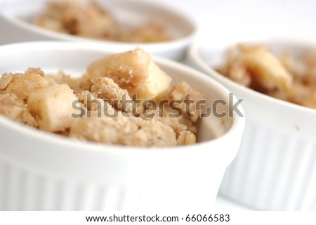 Home made apple crumble in white containers - stock photo