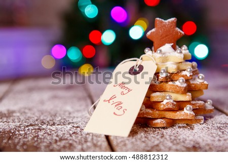 Home made baked Christmas gingerbread tree as a gift for family and friends on wooden background. With colorful lights from Christmas tree on background. With icing sugar Selfmade gift for xmas.