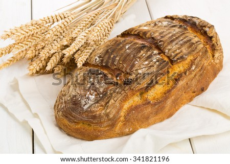 Home-made bread loaf with wheat ears on white wooden table background - stock photo
