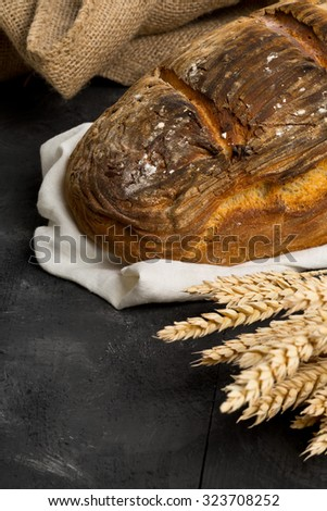 Home-made bread loaf with wheat ears on wooden table background - stock photo