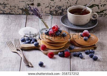 Home-made breakfast or brunch: american style pancakes served with berries and sugar powder on an old cutting board with a cup of black tea - stock photo