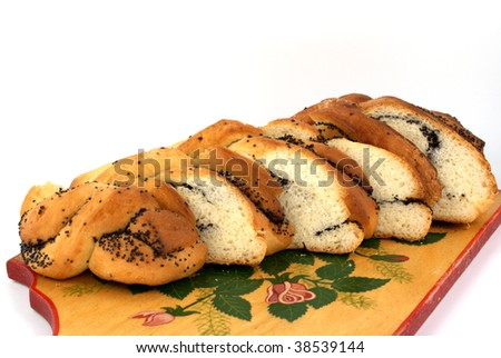 home-made bun with poppy seed on wooden plant on white background