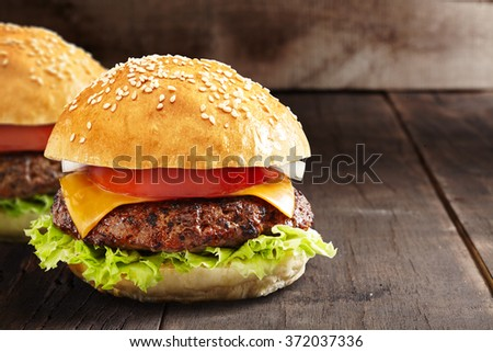 home made burger on a burned black wooden background