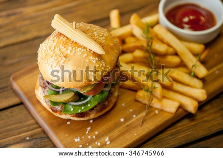 Home made burgers on wooden background with sauce - stock photo