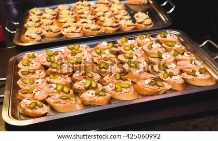 Home made canapes small sandwiches appetizers. Mix of different finger food snacks for a party or banquet on a plate.