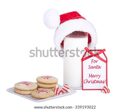 home made candy cane stripped peppermint flavor sugar cookies on a square plate with a glass of milk wearing a santa hat with a card saying for santa merry christmas - stock photo