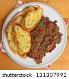 Home-made chilli con carne and garlic bread. - stock photo