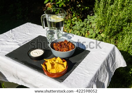 Home made Chilli Con Carne in orange ceramic bowl and tortilla chips and soured cream on the side with jug and glass of iced water. On slate mat, outside on linen covered table. Evening light - stock photo