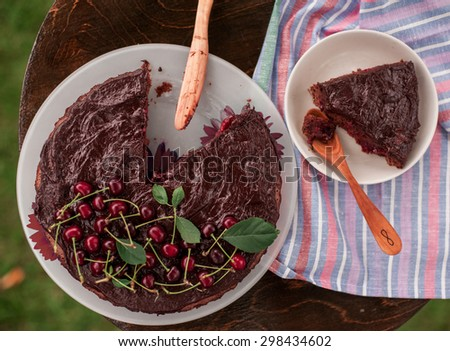 home made chocolate pie with cherries and hand carved wooden cutlery - stock photo