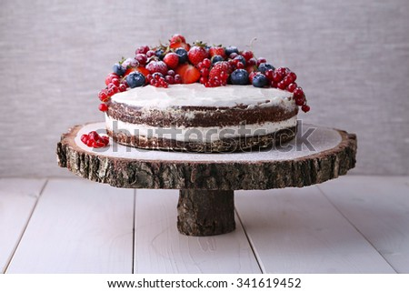Home made Earl Grey naked cake with cream cheese and berries and mashed strawberries in brandy inside on wooden cut stand and white neutral wood table - stock photo