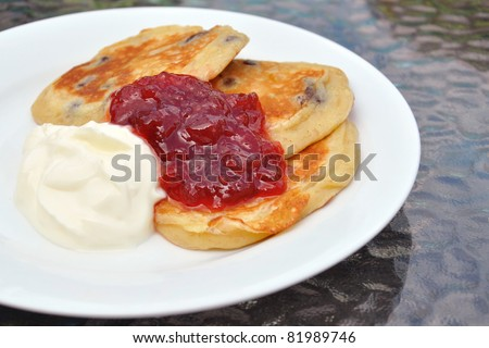 Home-made flippers, with jam and cream on white plate.