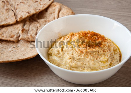Home made fresh hummus in white bowl with pita flat bread. A delicious and healthy mediterranean side dish or snack.