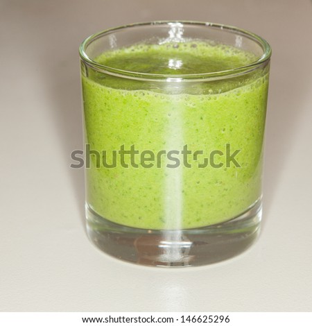 Home made fruit and vegetable smoothie blended from spinach, kale,celery, banana, orange, apple, pineapple and coconut juice. - stock photo