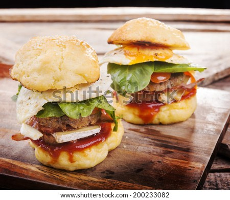 Home made gluten free mini burgers or sliders with beef, egg, lettuce, cheese and sauce - stock photo