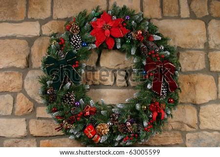 Home made holiday wreath hanging on stone wall - stock photo