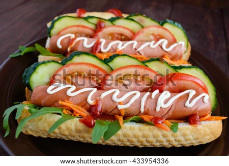 Home made hot dogs with vegetables, juicy sausage and arugula on the wooden background. Close-up. - stock photo