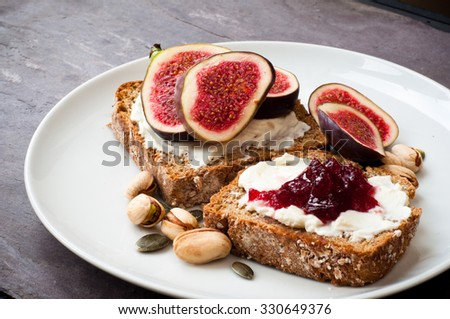 Home made Irish wheaten bread sliced and topped with cream cheese,fresh figs and jam. - stock photo