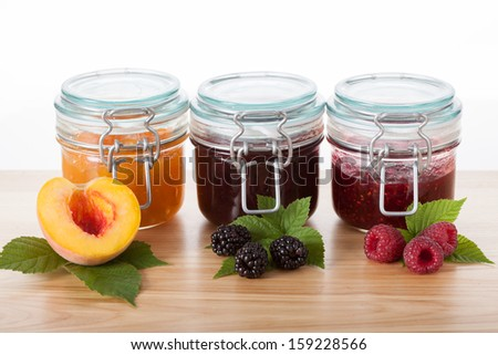 Home-made peach, blackberry and raspberry jams - stock photo