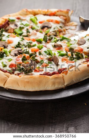 Home made pizza from scratch topped with mushrooms, turkey, kale, peppers, and tomatoes angled view - stock photo